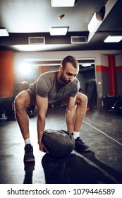 Strong man doing cross training with sandbag at the gym.