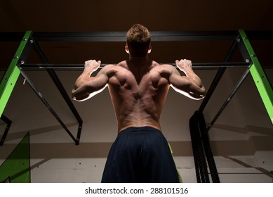 Strong man doing pull up in dramatic light. Dramatic light gives a motivated, focused, determined feel to the image.