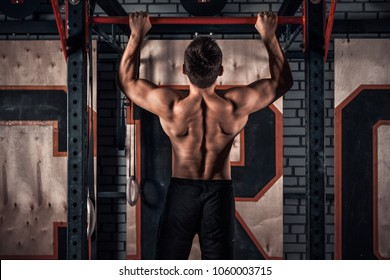 Strong man doing pull ups in gym