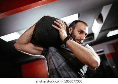 Strong man doing training with sandbag at the gym.