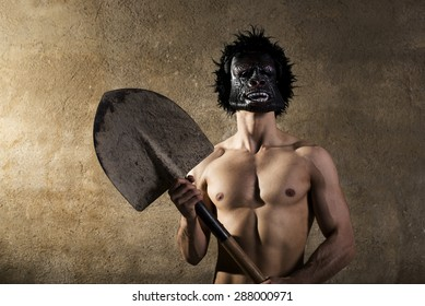 Strong man dressed like a monkey with a shovel to dig holes