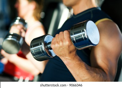 Strong man with dumbbells, in the background a woman also lifting weights; focus on hand and dumbbell