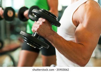 Strong man exercising with dumbbells in a gym, in the background a woman also lifting weights; focus on hands