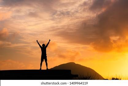 Starker Mann mit Faust in der Luft, der auf einem Berg steht. Triumph, Sieg und Gefühl entschlossen.