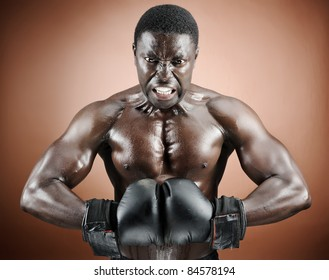 Strong man flexing pectoral and bicep muscles with boxing gloves in studio