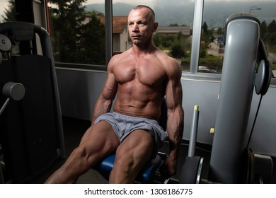 Strong Man In The Gym And Exercising Quadriceps And Glutes On Machine - Muscular Athletic Bodybuilder Fitness Model Exercise