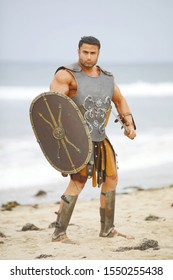 Strong man in historical armor, helmet with shield and sword posing on the beach