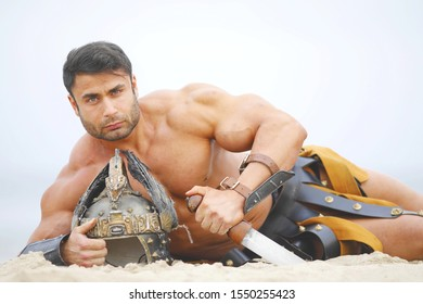 A strong man in historical armor lies on the beach with a sword and helmet