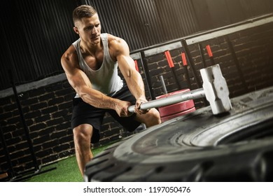 Strong man is hitting tire with a sledgehammer during his training workout