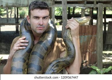 Strong man holding gigantic anaconda