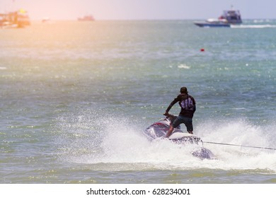 A strong man jumps on the jet ski above the water at sunset, Tropical Ocean, Vacation Concept