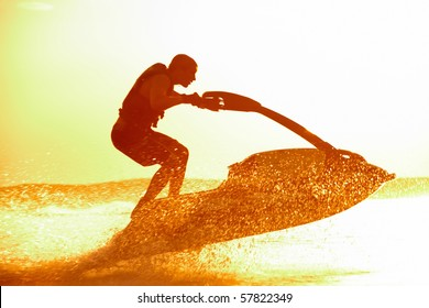 strong man jumps on the jetski above the water at sunset .silluet. spray.