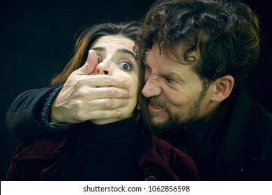 Strong man kidnapping young woman