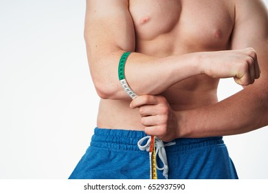 A strong man measures a hand a meter, a muscular man on a light background