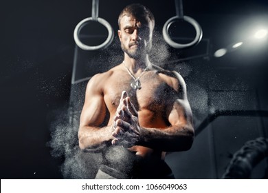 Strong man with muscles Claps his hands dust of magnesium workout. Concept cross, gymnast training