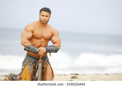 A strong man with a naked torso and historical armor with a sword poses on the beach