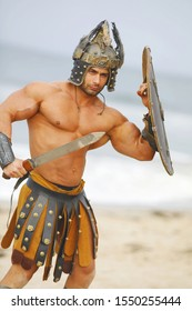 Strong man with a naked torso in historical armor, helmet with shield and sword posing on the beach+