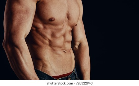 Strong man with naked torso showing his abdominal muscles over dark background.