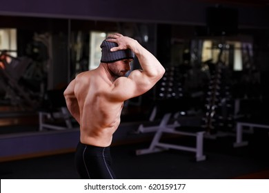 Strong man with perfect abs, shoulders, biceps, triceps and chest. Bodybuilder posing in gym, view from the back. Sport, training, motivation,willpower and lifestyle concept
