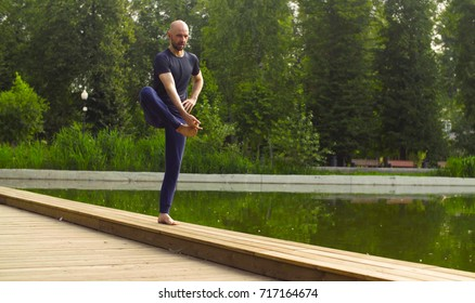 Strong man performing one-leg standing balance near the pond. Yoga asana - utthita hasta padagushthasana