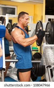 Strong man preparing his training machine in fitness club