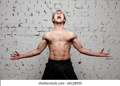 strong man  shouting and roaring against a brick wall