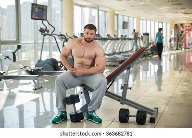 Strong man sitting on the bench in gym. Dumbbells on the floor. Girl on the background in gym.