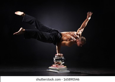The strong man is standing on the books