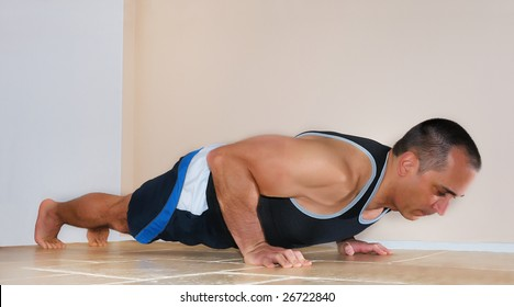 Strong man in tank top doing push ups on the floor.