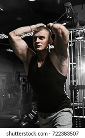 Strong man with tattoo working in gym