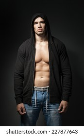 strong man wearing black hoody isolated on dark background