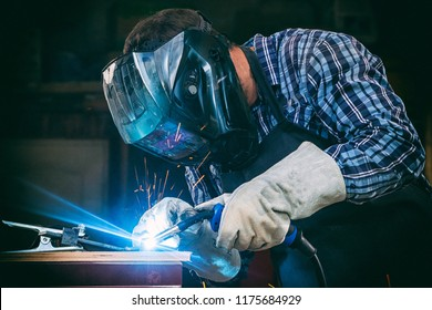 A strong man welder in a black T-shirt, in a welding mask and welders leathers weld metal welding machine in the workshop, in the sides fly the blue sparks