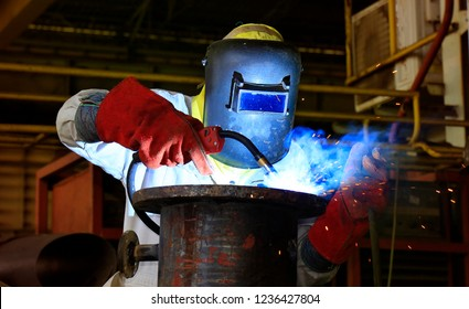 A strong man is a welder in a black T-shirt, in a welding mask and welders leathers,