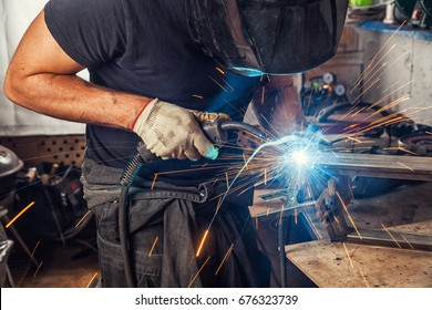 A strong man is a welder in a black T-shirt, in a welding mask and welders leathers, a metal product is welded with a welding machine in the garage, blue sparks fly to the sides
