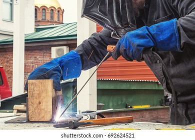 A strong man welder in a construction black overall and welding mask welds a welding machine with a mettalic construction in a wooden beam on the street, in the background an old red brick building