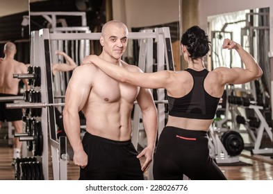 Strong man and a woman posing in a gym