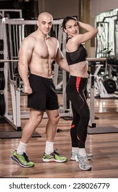 Strong man and a woman posing in a gym , showing their biceps