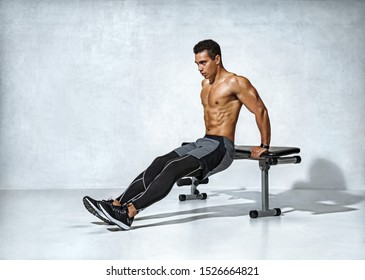 Strong man working out arms muscles doing triceps dips using bench. Photo of latin man with perfect body on grey background. Strength and motivation