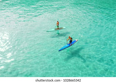 Strong men floating on a SUP boards in a beautiful bay on a sunny day. Aerial view of the men crosses the bay using the paddleboard. Water sports, competitions. Nai Harn beach, Phuket, Thailand.