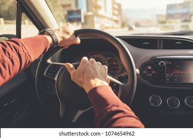 Strong men's hands in burgundy shirt holding the steering wheel of the car and pushes on the signal overlooking the blurred city
