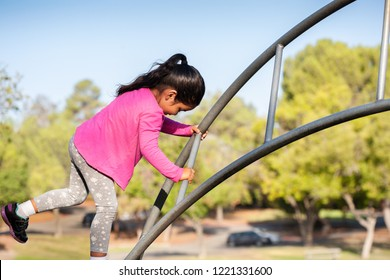 A strong mexican girl climbing a challenge bridge in a kids playground at an outdoor park who is wearing a pink colored shirt.