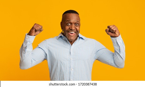 Strong middle aged african american man showing biceps at camera, orange panorama background