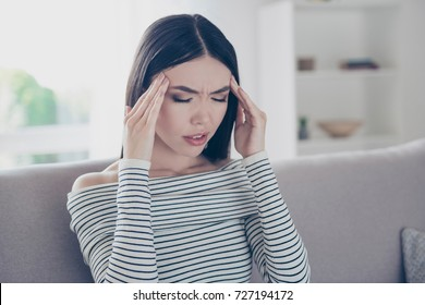Strong migraine blast, suffer. Close up cropped photo of young chinese lady, sitting on beige couch indoors at home, wearing casual striped outfit, suffering from pain, ache is very hard