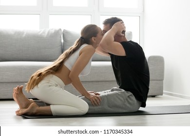Strong millennial man work out, do situps on mat at home kissing girlfriend, perform abs exercises while training with woman lover, fit couple workout together motivating and encouraging for crunches