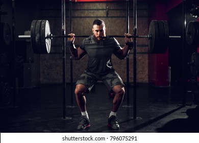 Strong motivated and focused muscular bearded short hair bodybuilder man holding a heavyweight barbell on the shoulder behind the neck while crouching and doing squats exercise in the dark gym.