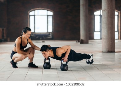 strong motivated man doing plank with kettlebells during workout at gym while his girlfriend looking at him. hobby, interest, motivation