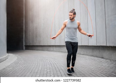 Strong and muscled young man jumping and using rope for that. He looks to left. Guy is calm and concentrated on doing excercise. He is alone there.