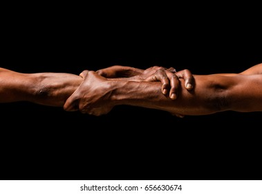 Strong and muscular African hands gripping outstretched arms.