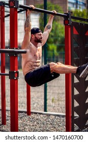 Strong Muscular bearded man doing abdominal exercise on horizontal bar at street gym yard. Strength and motivation. Outdoor workout. fitness, sport, exercising, training and lifestyle concept .
