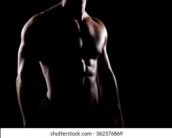 Strong and muscular body of man shaded over black background.